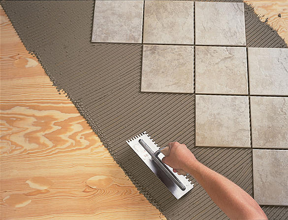 Процесс укладки плитки на фанерное основание